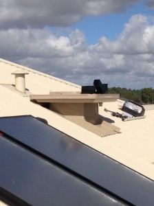 Halfway through an installation of a coolbreeze heritage unit on a cream colorbond roof in Byford, Perth